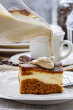 Pouring caramel sauce on piece of cake Stock Image