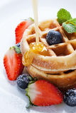 Pouring caramel sauce on waffles with strawberry and blueberry Royalty Free Stock Photos