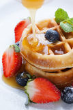 Pouring caramel sauce on waffles with strawberry and blueberry Stock Image