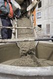 Pouring cement. Truck operator pouring cement into crane bucket Stock Photo