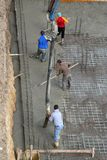 Pouring Cement. Workers at the time of pouring cement on the foundations of a house under construction Stock Image
