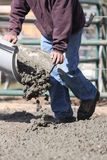 Pouring cement for a day. Man guiding cement chute with wet cement coming out stock photo
