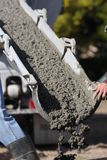 Pouring cement wet. Man guiding cement chute with wet cement coming out Stock Images