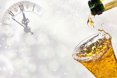 Pouring champagne against holiday lights Royalty Free Stock Images