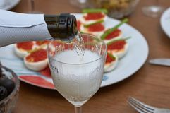 Pouring champagne from a bottle into a glass on the background of red caviar, close-up. Pouring champagne from a bottle into a glass on the background of red stock images
