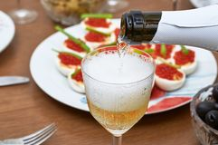 Pouring champagne from a bottle into a glass on the background of red caviar, close-up. Pouring champagne from a bottle into glass on the background of red royalty free stock images