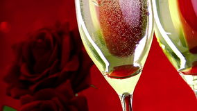 Pouring champagne flutes with bubbles near red roses on red bokeh background, love and valentine day concept. Dolly camera movement stock video