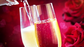 Pouring champagne into flutes with gold bubbles with abstract glitter sparkle particles flowing and red hearts shape background stock footage