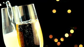 Pouring champagne into flutes with golden bubbles with golden abstract blinking blurred Christmas tree lights bokeh