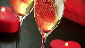 Pouring champagne flutes near red candles burning, love and valentine day stock video