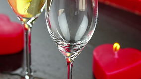 Pouring champagne flutes near red candles burning, love and valentine day concept. Dolly camera movement stock footage