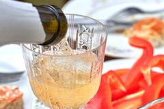 Pouring champagne into the glass from the bottle royalty free stock photos