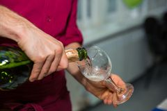 Pouring champagne into glass at hen-party, close up. Restaurant feed. New Year Christmas Royalty Free Stock Photography
