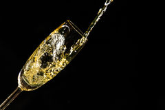 Pouring champagne. Into a glass isolated on black background. New Year Celebration Royalty Free Stock Photo