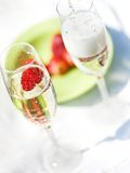 Pouring champagne into glass with strawberry Stock Images