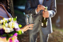 Pouring champagne into a glass on a wedding celebration Stock Photography
