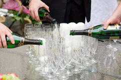 Pouring champagne into glasses. Three hands pouring champagne into glasses - celebration preparation stock photo