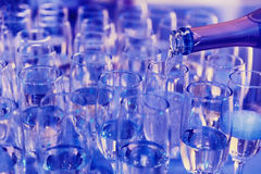Pouring champagne into a glasses. With bubbles Stock Images