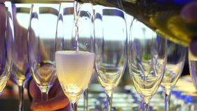 Pouring champagne into a glasses standing on table. Champagne filling in glasses standing on the table, close-up video stock video footage