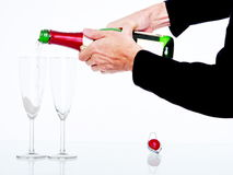 Pouring champagne. Champagne pouring in two glasses Royalty Free Stock Photo