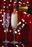 Pouring champagne in two glasses from bottle on festive backgrou Stock Image