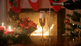 Pouring champagne in two glasses on Christmas dinner table. Burning fireplace at background stock video