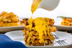 Pouring a cheese sauce over crispy hash browns. Pouring a rich cheese sauce from a white jug, over a stack of golden crispy hash browns on a plate in a close up stock photography