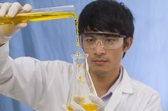 Pouring chemicals. Student Scientist pouring chemicals in a laboratory Royalty Free Stock Images