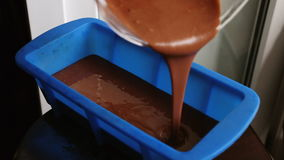 Pouring chocolate bakery dough into blue silicone pan stock video