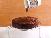 Pouring chocolate icing. Over chocolate sponge cake stock images