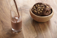 Pouring chocolate milk in glass with homemade chocolate cookies with hazelnuts on background Stock Photo