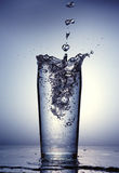 Pouring of clean water in a clear glass. On a light gradient backgound Stock Image