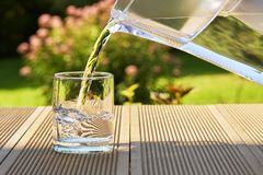 Free Pouring Clear Filtered Water From A Water Filtration Jug Into A Glass In Green Summer Garden In A Sunny Summer Day Royalty Free Stock Photos - 133009998