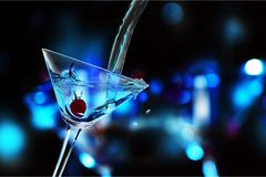 Pouring martini cocktail on dark background stock image
