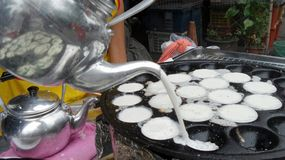 Pouring Coconut milk from kettle on Thai Coconut Pudding Kanom Krok Royalty Free Stock Photography