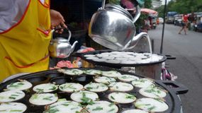 Pouring Coconut milk from kettle on Thai Coconut Pudding Kanom Krok Royalty Free Stock Images