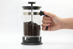 Pouring coffee beans into the mug Stock Images
