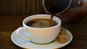 Pouring coffee from coffee cezve turka into the cup on wooden table. stock video footage