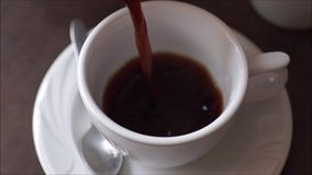 Pouring coffee into cup. From above stock footage