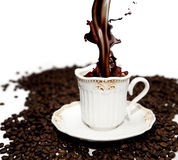 Pouring coffee. Cup of coffee on coffee beans  on white Stock Photo