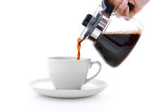 Pouring coffee on a cup isolated on white Royalty Free Stock Images