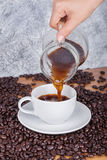 Pouring coffee in a cup. On wooden table Royalty Free Stock Images