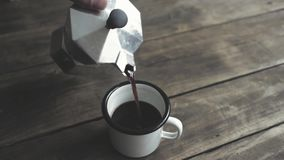 Pouring coffee into enamel mug stock video
