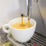 Pouring a coffee espresso on a machine in a white mug Royalty Free Stock Photography