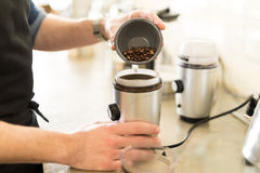Pouring coffee grains on a grinder. Closeup of a male barista pouring some coffee grains on a grinder to make a cup of coffee Stock Photography