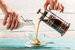 Pouring coffee and milk into a cup Stock Photo