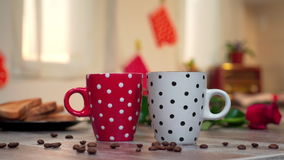 POURING COFFEE FROM THE POT INTO TWO CUPS, ROMANTIC BACKGROUND. POURING COFFEE FROM THE POT IN RED AND WHITE CUP WITH DOTS. BEANS OF COFFEE ON THE TABLE stock video footage