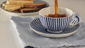 Pouring coffee into a striped cup. Pouring black coffee into a striped cup on a domestic kitchen stock video