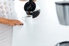 Pouring coffee to a coffee cup Stock Photos