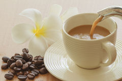 Pouring coffee in to cup and grains Royalty Free Stock Photos